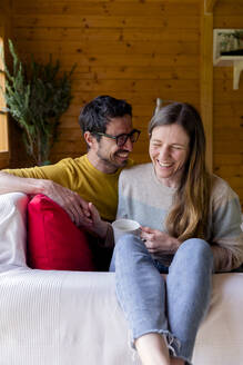 Cheerful couple holding hands while relaxing on sofa in log cabin - LVVF00012