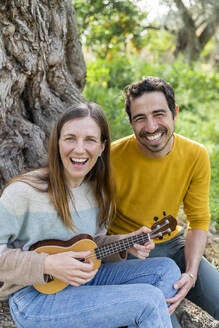 Cheerful woman playing guitar while sitting with boyfriend against tree at countryside - LVVF00027