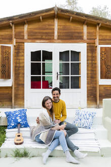 Smiling couple sitting on steps against log cabin - LVVF00054