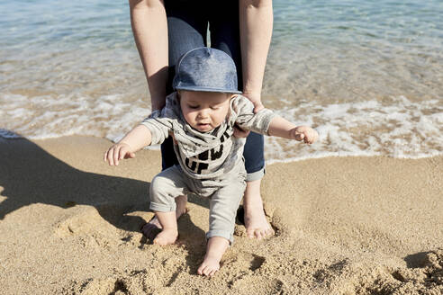 Low section of mother assisting son in walking on sandy beach - JNDF00162