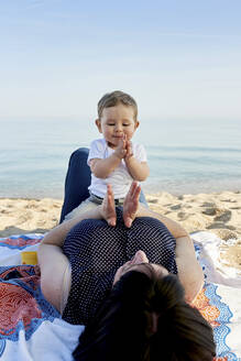 Mother playing clapping game with cute son while lying on blanket at beach against sea - JNDF00165