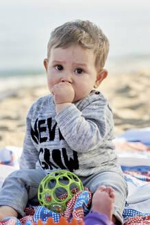 Cute boy sucking thumb while sitting on blanket at beach - JNDF00171