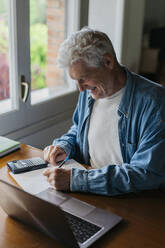 Happy senior man writing on paper while using calculator and laptop at home - AFVF06543