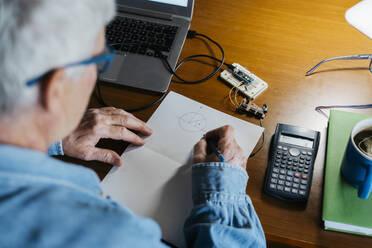 Senior man making diagram on paper while repairing laptop at home - AFVF06549