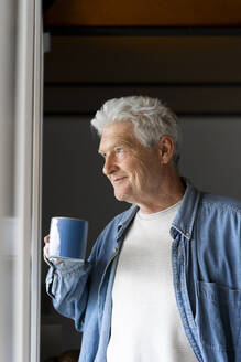 Thoughtful senior man smiling while drinking coffee by window at home - AFVF06552