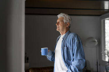 Thoughtful senior man holding coffee mug while looking through window at home - AFVF06555