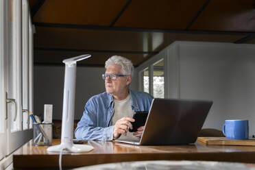 Thoughtful senior man holding smart phone with laptop on table at home - AFVF06558