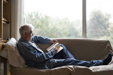 Senior man reading book while relaxing on sofa by window at home - AFVF06561