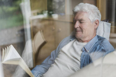 Senior man reading book while relaxing on sofa seen through glass window - AFVF06567