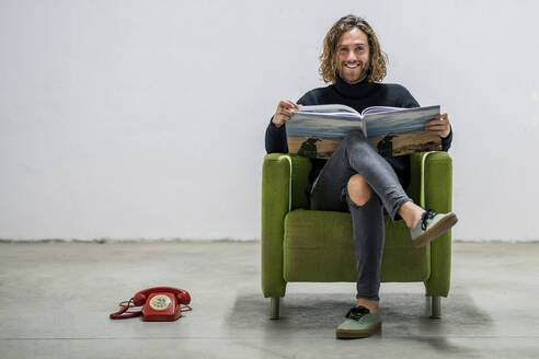 Smiling young man with book sitting on armchair against wall at home - DLTSF00717
