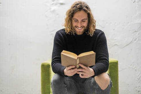 Smiling man reading book while sitting on armchair against wall at home - DLTSF00723