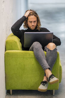Young man with hand in hair using laptop while sitting on armchair at home - DLTSF00726