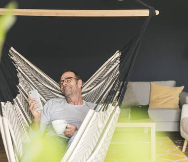 Happy man using smart phone while sitting with coffee cup on hammock at home - UUF20444