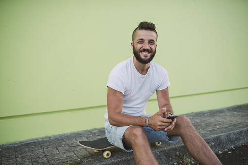 Smiling young man holding smart phone while sitting on skateboard - RAEF02381