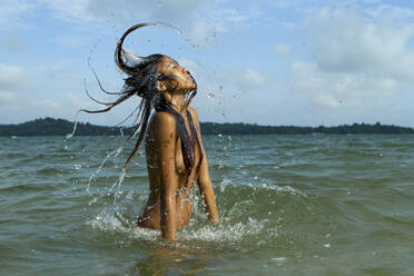 Topless sensuous young woman tossing hair while standing in sea against sky - EAF00020