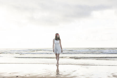 Young woman wearing white dress walking at shore against sea - FVSF00387