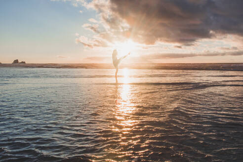 Silhouette woman dancing while standing in sea against sky during sunset - FVSF00399