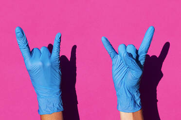 Latex sanitary gloves doing rock and roll signal on pink background - GEMF03834