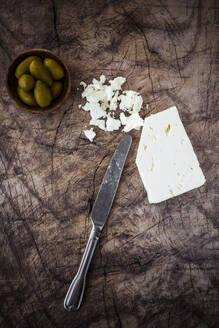 Feta cheese, bowl of fresh olives and table knife on wooden surface - GIOF08350