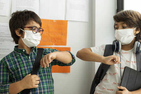 Boys wearing masks giving elbow bump while standing against wall in school - VABF02988