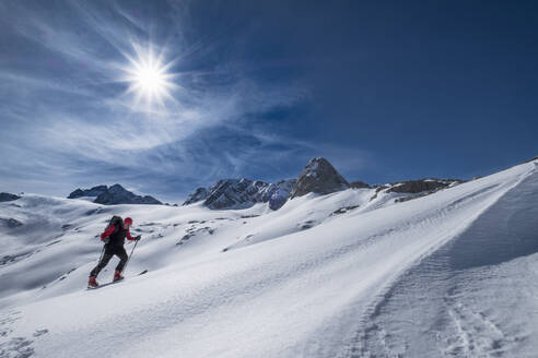 Man skiing on snow covered Dachstein mountain against sky during sunny day, Austria - HAMF00628