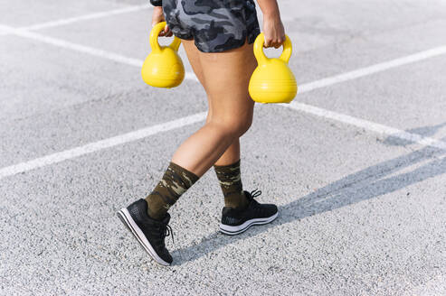 Young woman holding kettlebells while walking on road - JCMF00788
