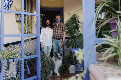 Couple wearing masks with dog standing at entrance of house seen through gate - AGGF00072