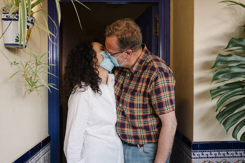 Romantic couple wearing masks kissing while standing at entrance - AGGF00078