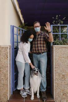 Man wearing mask waving hand while woman looking at dog - AGGF00084
