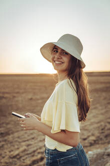 Happy young woman holding smart phone while standing on field against clear sky during sunset - ACPF00750