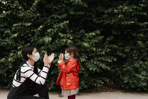 Mother and daughter wearing masks while playing clapping game against plants - EGAF00122
