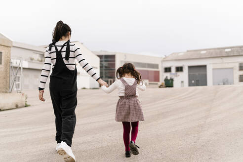 Mother and daughter holding hands while walking on street - EGAF00131