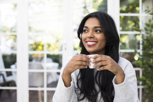 Thoughtful young woman smiling while holding coffee cup at cafe - ABZF03166