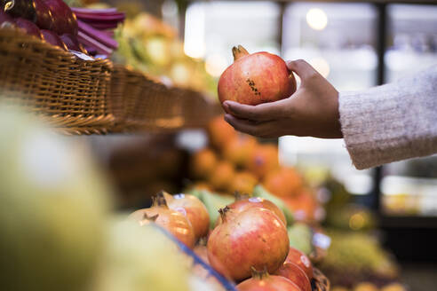 Cropped image of woman buying pomegranate at grocery store - ABZF03175