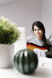 Happy young woman using laptop while sitting with electric guitar at home - JMHMF00052