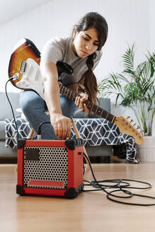 Woman adjusting knobs on amplifier while playing electric guitar at home - JMHMF00058
