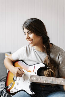 Happy woman playing electric guitar while sitting at home - JMHMF00061
