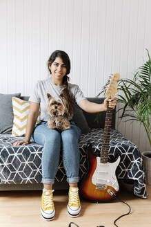 Happy young woman holding electric guitar while sitting with Yorkshire Terrier on sofa at home - JMHMF00064