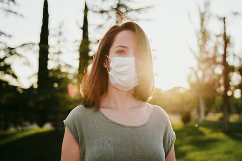 Portrait of pensive woman wearing protective mask in nature - EBBF00180