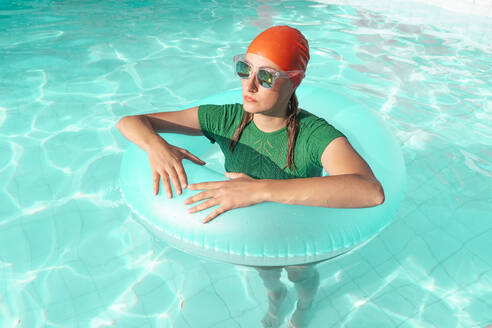 Portrait of woman with floating tire standing in swimming pool - ERRF03977
