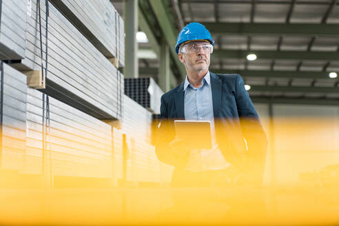 Mature businessman with tablet wearing hard hat and safety goggles in a factory - MOEF02907