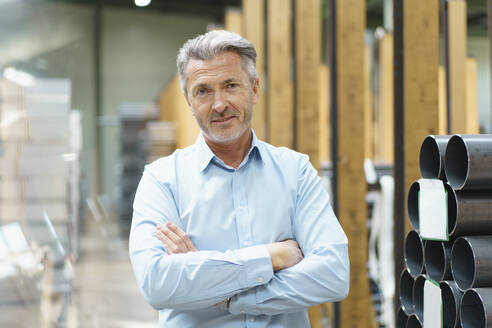 Portrait of a confident mature businessman in a factory storehouse with steel pipes - MOEF03078