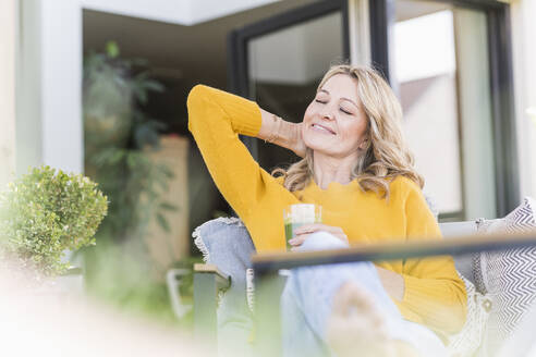Portrait of smiling mature woman relaxing on terrace with green smoothie - UUF20536