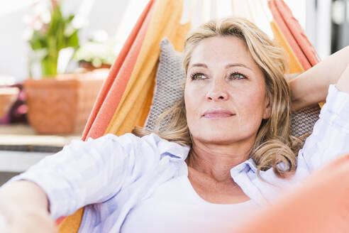 Portrait of pensive mature woman relaxing in hammock - UUF20584