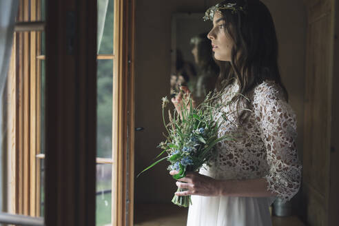Young woman in elegant wedding dress holding bouquet looking out of the window - ALBF01260