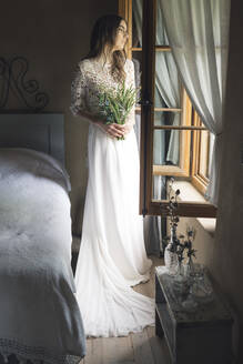 Young woman in elegant wedding dress holding bouquet looking out of the window - ALBF01263