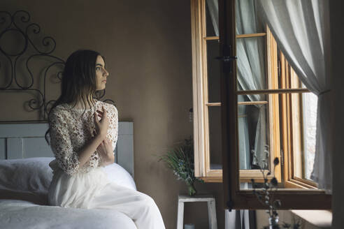 Young woman in elegant wedding dress sitting on bed looking out of the window - ALBF01266