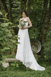 Young woman in elegant wedding dress with bouquet standing on bench - ALBF01269