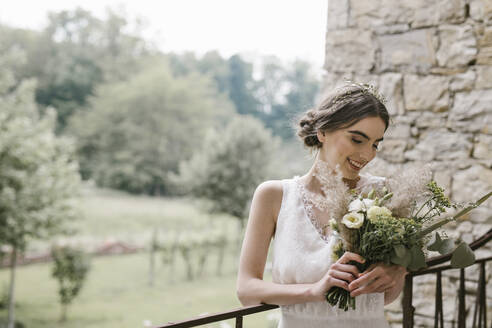 Young smiling woman in elegant wedding dress and bouquet - ALBF01281