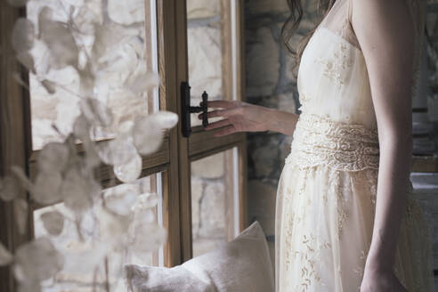 Young woman in elegant wedding dress opening window - ALBF01284